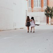 Two little girls walking with arms around each other.