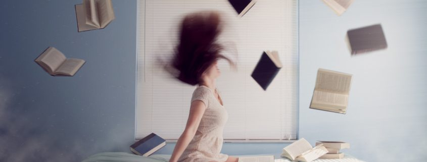Girl on bed surrounded by books in the air