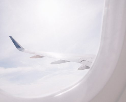 Out the oval window of an airplane looking at the wing.